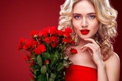 Hållande bukett för härlig blond kvinna av röda rosor Internationell dag för kvinna` s åtta beröm för mars Arkivbild