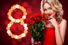 Hållande bukett för härlig blond kvinna av röda rosor på bokehbakgrund Internationell dag för kvinna` s åtta mars Arkivbilder