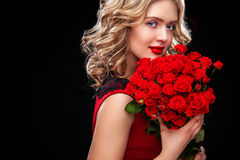 Hållande bukett för härlig blond kvinna av röda rosor Sankt valentin och internationell dag för kvinna` s, åtta mars Royaltyfri Bild