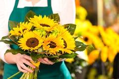 Hållande bukett för kvinnlig blomsterhandlare av solrosor Royaltyfria Foton