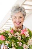 Hållande bukett för pensionerad kvinna av blommor som ler på kameran Royaltyfria Bilder