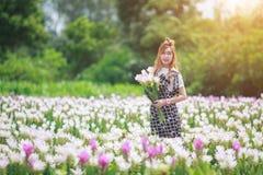 Hållande bukettblommor för härlig flicka Stående i naturfält Royaltyfri Fotografi