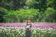Hållande bukettblommor för härlig flicka Stående i naturfält Arkivfoto
