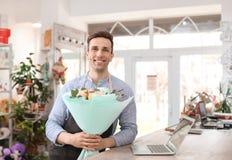 Hållande bukettblommor för manlig blomsterhandlare Fotografering för Bildbyråer