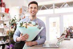 Hållande bukettblommor för manlig blomsterhandlare Arkivbilder