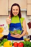 Hållande bunke för hemmafru av nya sallad- och visningtum upp Royaltyfri Foto