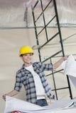 Hållande byggnadsplan för lycklig mitt- vuxen arbetare, medan se bort Royaltyfri Bild