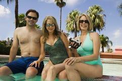 Hållande camcorder för kvinna med par på simbassängståenden. arkivbild