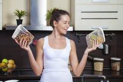 Hållande cans för ung lycklig kvinna av sädesslag i köket arkivbilder