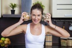Hållande cans för ung lycklig kvinna av sädesslag i köket royaltyfri foto