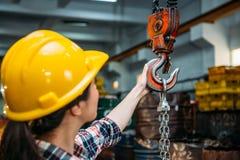 Hållande chain kran för industriell fabrikskvinna Royaltyfri Bild