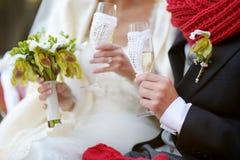 Hållande champagneexponeringsglas för brud och för brudgum Arkivfoto