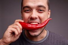 Hållande chilipeppar för man i hans tänder Rolig grabb som äter varm kryddig peppar på en grå bakgrund band för mått för äpplebeg Royaltyfri Foto