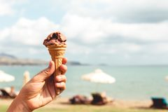 Hållande chokladglass för hand på stranden royaltyfri foto