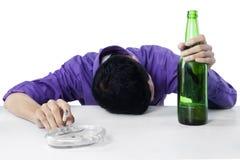 Hållande cigarett för berusad man och flaska av öl Arkivfoto