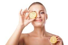 Hållande citronskiva för kvinna som är främst av öga royaltyfria bilder