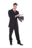 Hållande clapperboard för affärsman Fotografering för Bildbyråer