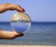 Hållande crystal jordklot för mänsklig hand Arkivbilder