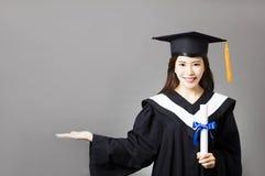 hållande diplom för ung kandidat med visninggest royaltyfria bilder