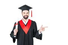 Hållande diplom för ung student och peka bort med fingret på vit Arkivfoto