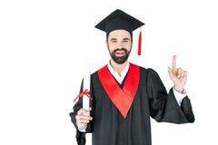 Hållande diplom för ung student och peka upp med fingret Royaltyfri Bild