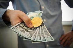Hållande dollar för ung affärsman och mynt av bitcoin i hand royaltyfri foto