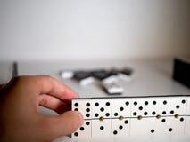 Hållande dominobricka för hand Den första personen pekar av beskådar Begrepp av domino royaltyfria bilder