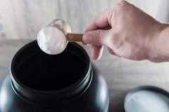 Hållande doser för hand och hällande mattillägg Arkivfoto