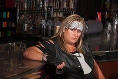 Hållande drinkexponeringsglas för Grumpy kvinna royaltyfri bild