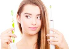 Hållande elkraft för kvinna och traditionell tandborste Royaltyfria Bilder