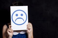 Hållande emoticon för kvinna - sorgsenhet royaltyfri fotografi