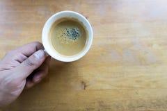 Hållande espressokaffe för hand i den vita koppen med kopieringsutrymme Arkivfoto