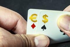Hållande euro och dollar som spelar kort Arkivfoto