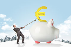 Hållande eurotecken för affärsman med repet och staden Arkivbild