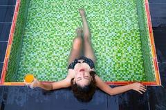 Hållande exponeringsglas för asiatisk flicka av orange fruktsaft i henne händer som ligger i simbassängen Fotografering för Bildbyråer