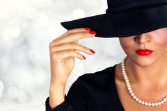 Hållande exponeringsglas för attraktiv kvinna av vitt vin Stående av en härlig flicka som bär den svarta hatten Royaltyfri Foto