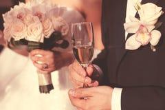 Hållande exponeringsglas för brud och för brudgum av vin fotografering för bildbyråer