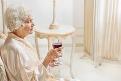 Hållande exponeringsglas för ensam mogen kvinna av alkoholdrycken royaltyfria bilder