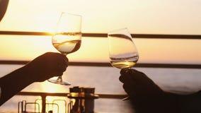 Hållande exponeringsglas för folk av vin, danande ett rostat bröd över solnedgång Parti utomhus tycka om tid tillsammans royaltyfria foton