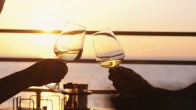 Hållande exponeringsglas för folk av vin, danande ett rostat bröd över solnedgång Vänner som dricker vitt vin som rostar finka Pa arkivbild
