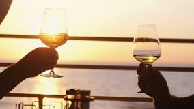 Hållande exponeringsglas för folk av vin, danande ett rostat bröd över solnedgång Vänner som dricker vitt vin som rostar finka Pa arkivfoton