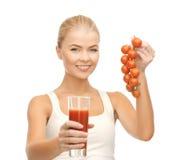 Hållande exponeringsglas för kvinna av fruktsaft och tomater Royaltyfria Bilder