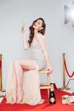 Hållande exponeringsglas för kvinna med champagne på röd matta Arkivfoto