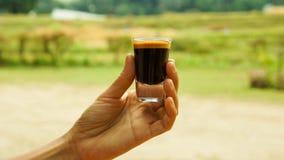 Hållande exponeringsglas för kvinnahand av det varma espressoskottet Royaltyfria Bilder