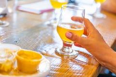 Hållande exponeringsglas för kvinnlig hand av mikrobrygdöl på stången royaltyfri fotografi