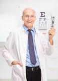 Hållande exponeringsglas för mogen optiker i hans kontor royaltyfri bild
