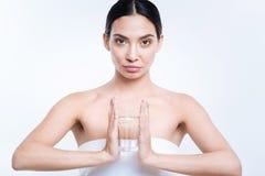 Hållande exponeringsglas för spenslig kvinna av vatten mellan henne händer Fotografering för Bildbyråer