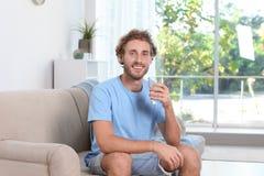Hållande exponeringsglas för ung man av rent vatten arkivbilder