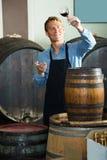 Hållande exponeringsglas för vinproducent av vin i källare Royaltyfri Foto
