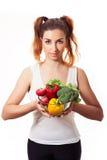 Hållande exponeringsglasbunke för Redheaded caucasian flicka med söta peppar för fres, rädisan, broccoli och grönsallat Arkivbild